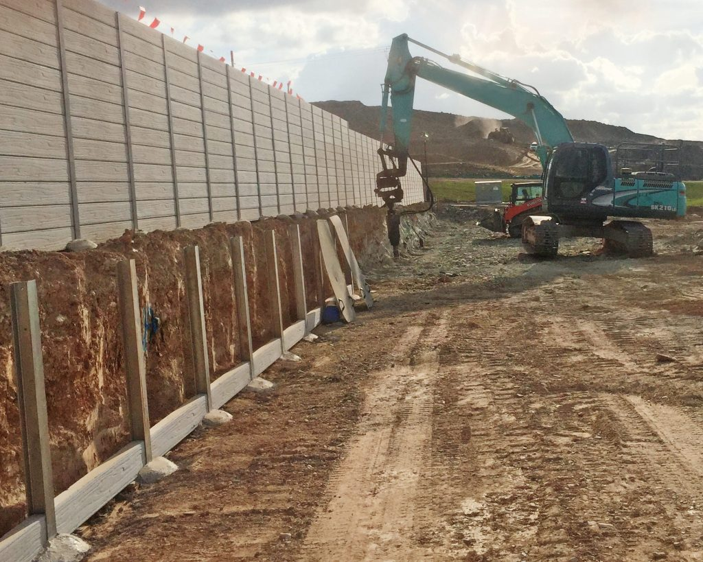 concrete sleeper retaining wall during installation by urban retaining walls