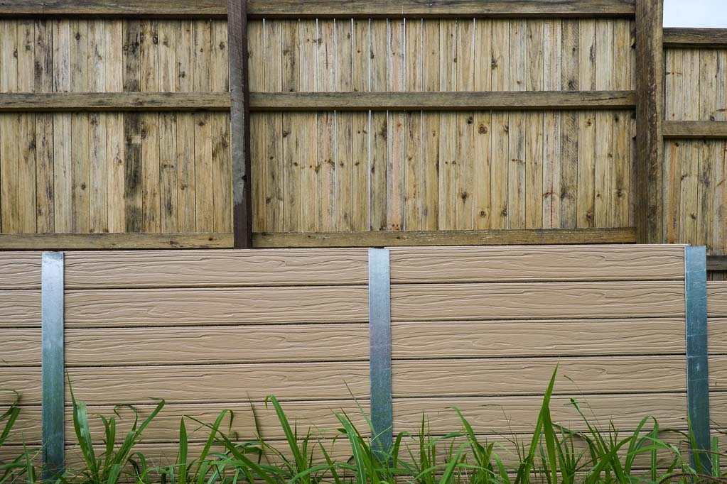 Two tier fence with concrete sleeper retaining wall and timber fence